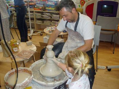 Nuestro alfarero ayuda a los niños a realizar figuras de barro en el torno