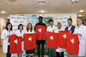Jaylen Brown, jugador de la NBA, posa con delegada de Salud y equipo directivo con la camiseta roja de la donación de órganos