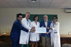 Responsables del hospital y el IMIBIC recepcionan el cheque que entrega la Federación de Peñas