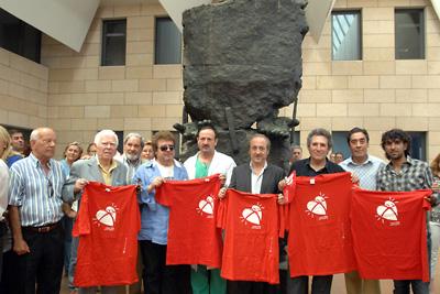 Todos los invitados con la camiseta delante del monumento al donante.