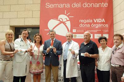 Espartaco muestra su carné de donante junto a la delegada de Salud y responsables del hospital.