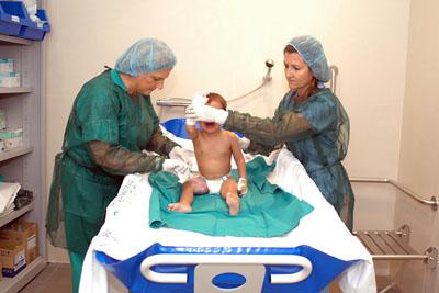 La doctora Paredes y una enfermera realizan curas a un bebé con quemaduras