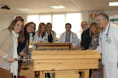 Responsables educativos y sanitarios alrededor del futbolín donado al hospital