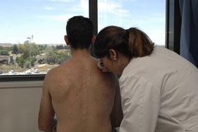 Dermatóloga del Hospital Reina Sofía realiza un examen cutáneo a un paciente
