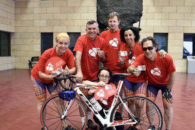 Ciclistas de la Federación Internacional de Deportistas Trasplantados posan delante del Monumento al donante con la camiseta y la tarjeta de la donación