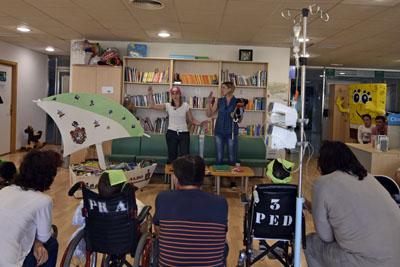 En la imagen, la autora e ilustradora del cuento 'La Isla Trospilanda' interprentan el texto a los niños hospitalizados
