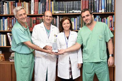 En la imagen, profesionales del equipo que participó en la realización de un trasplante hepático auxiliar de donante vivo por vía laparoscópica en paciente pediátrico y la directora gerente del hospital, Valle GArcía, sostienen el galardón recibido