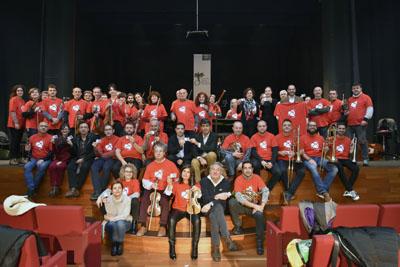Autoridades, profesionales del hospital, personal artístico y técnico de la Orquesta de Córdoba posan con la camiseta de la donación en el escenario del Teatro Góngora