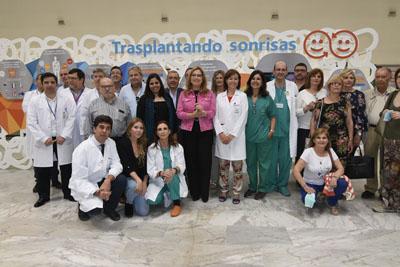 Profesionales, pacientes y autoridades posan tras la inauguración de la muestra 'Trasplantando Sonrisas'