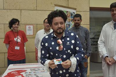 El cantaor flamenco Rafael de Utrera posa con el carné de donante