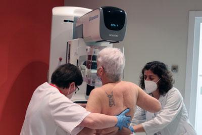 Técnico y enfermera ayudan a paciente para realizarse una mamografía