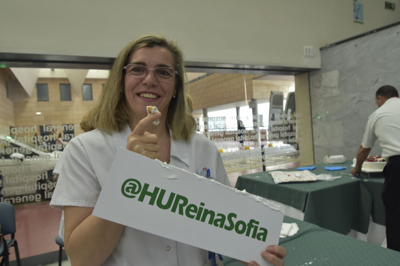 Una profesional del hospital prueba la tarta del aniversario