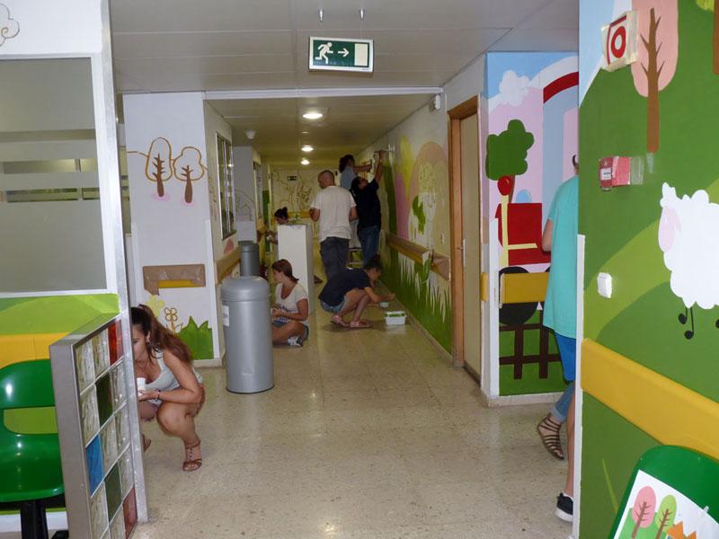 Voluntarios trabajando en el mural de los cerditos