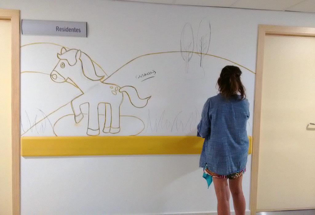 Una de nuestras diseñadoras, Mariló dibujando el Mural de los caballos