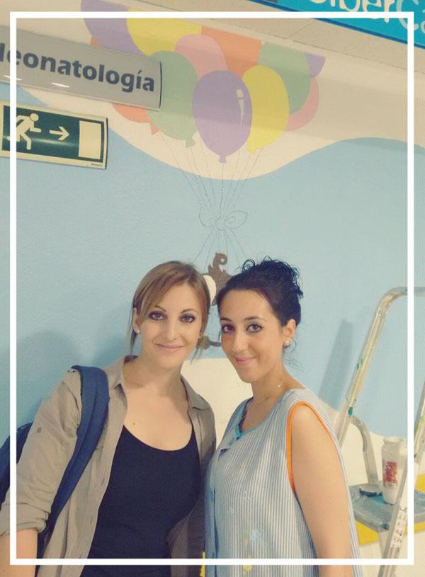 """Una de las diseñadoras María, junto con una voluntaria, en el mural de """"El mono lolo bebé"""""""