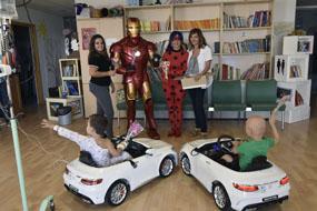 Iron Man, Lady Bug posan con los dos coches donados por la ONG Por la sonrisa de un niño