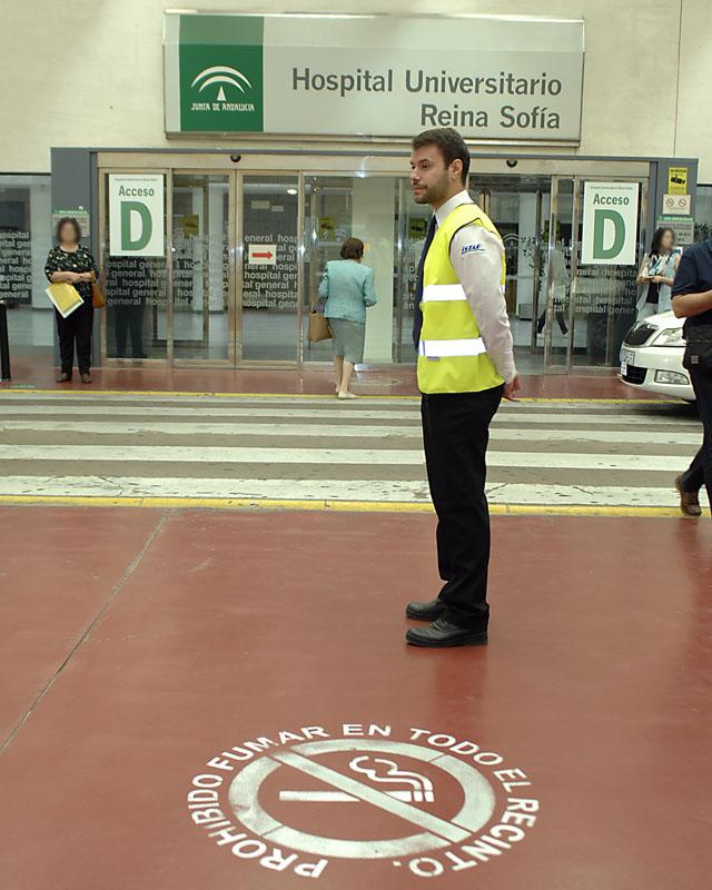 Personal de Seguridad ofrece información contra el tabaquismo a las personas que transitan por la calle interior cubierta del Hospital Reina Sofía.