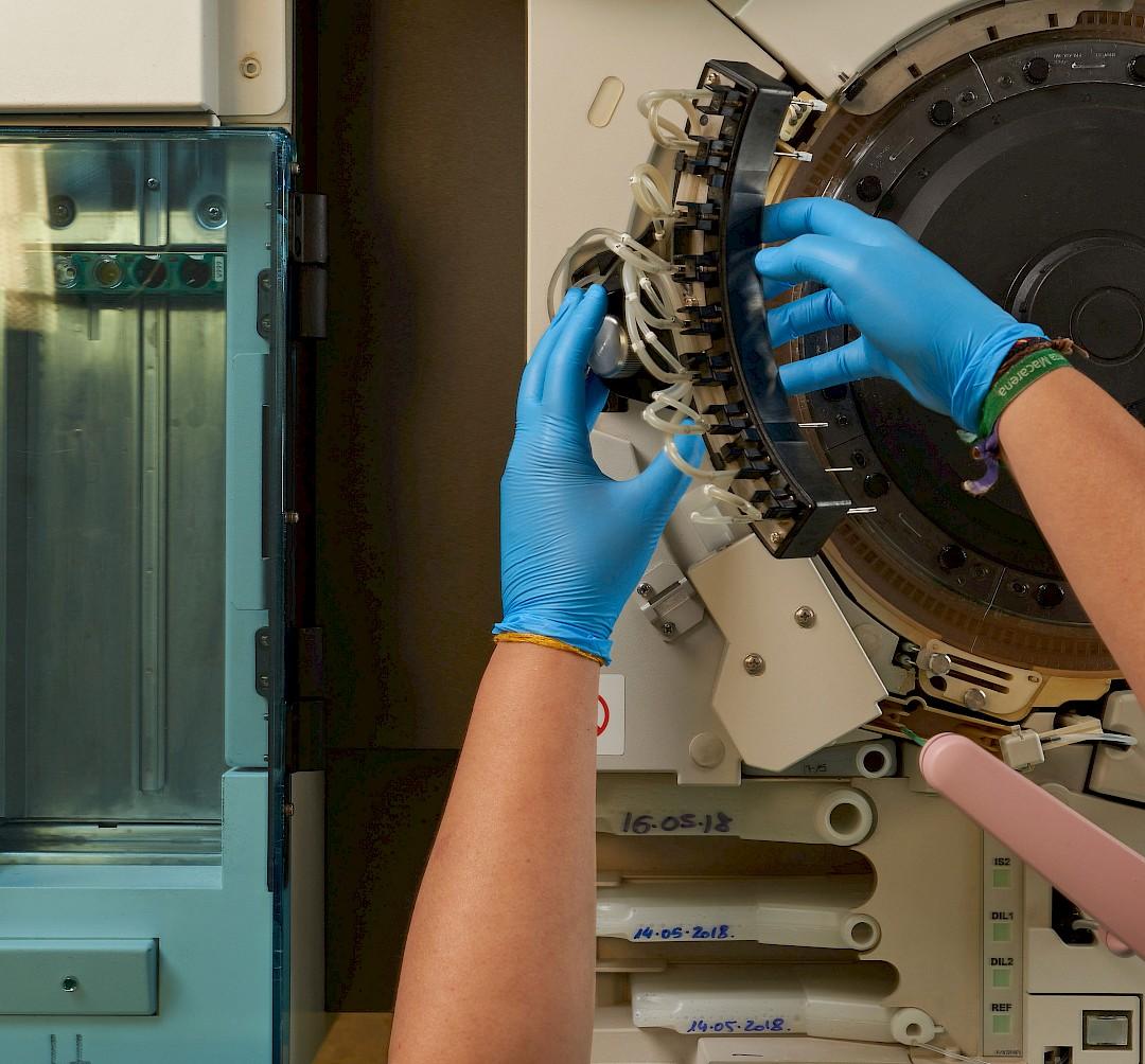 Foto de unas manos manipulando una máquina en laboratorio.