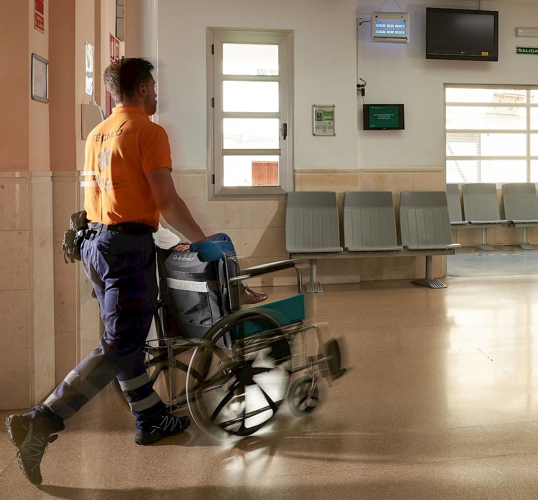 Foto de un trabajador llevando una silla de rueda de urgencias.
