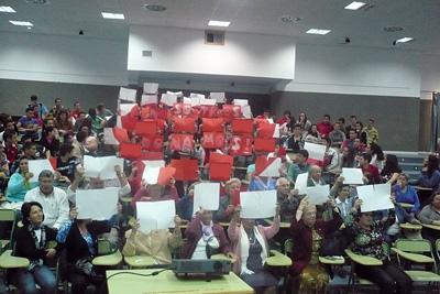 Asistentes al acto forman en corazón de papel rojo con la inscripción 'nosotr@s donamos'