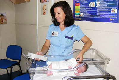 La auxiliar de enfermería Ana Izquierdo realiza una prueba acústica a un bebé.