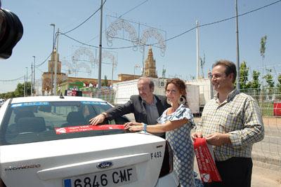 El gerente, la delegada de Salud y el presidente del colectivo del taxi colocan el adhesivo.