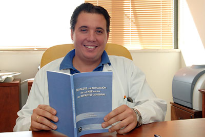 El doctor Ochoa muestra el manual que él ha coordinado