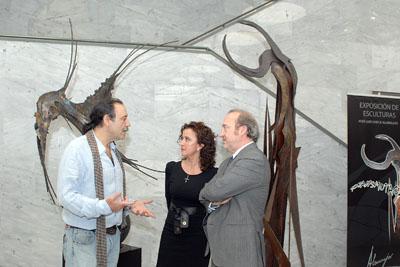 El artista explica a la delegada y al gerente su proceso creativo.