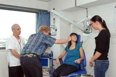 Médico checo realiza una exploración de oido con un microscopio.
