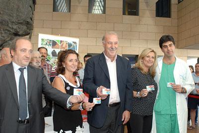 Vicente del Bosque, en el centro, muestra su tarjeta de donante.