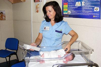 Una auxiliar de enfermería realiza una de las pruebas de audición a un bebé