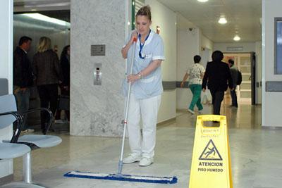 Limpiadora del hospital coloca indicación de suelo mojado para evitar posibles rebalones