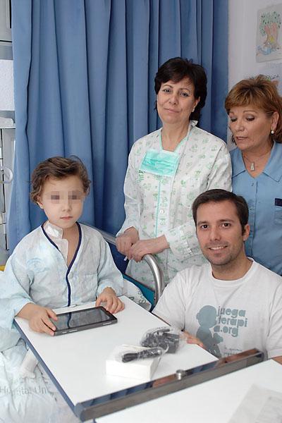 Una paciente, junto a profesionales sanitarios y de Juegaterapia, disfrutando de su regalo