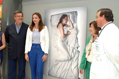 La donante Lourdes Cubero, junto a su retrato de la exposicón 'Hágase la luz'