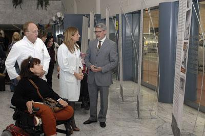 La gerente del hospital atiende a las explicaciones del profesor durante la inauguración de la exposición