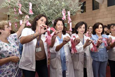 Profesionales del hospital que han superado un cáncer de mama cuelgan un lazo con su nombre