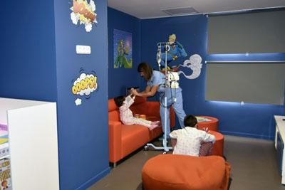 Dos niños ingresados juegan con una enfermera en el Salón de Héroes