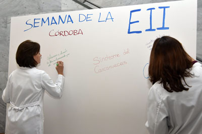 Valle García y Eva Iglesias escriben mensajes a los pacientes con EII en el vestíbulo del hospital General
