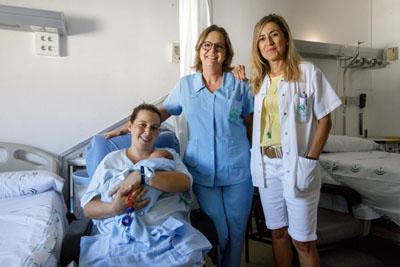 Una mamá que acaba de dar a luz, junto a profesionales del hospital