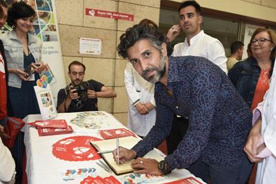 Arcángel firma en el libro de oro de la Donación