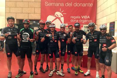 El equipo 'Kilómetros de Vida' posa con el carné de donante