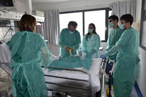 Lorenzo Pérez practica una cura a un paciente en la Unidad de Cuidados Intensivos