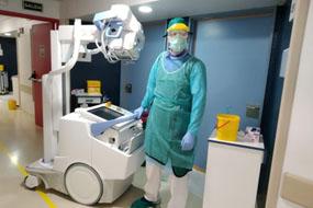 Tecnico especialista en radiologia con el equipo en unidad covid de hospitalizacion