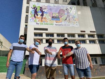 El artista urbano Sake, junto a los menores que han participado en el mural
