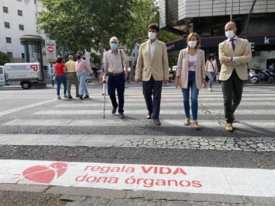 Responsables sanitarios y persona trasplantada cruzan el paso de peatones que luce el logo de la donación
