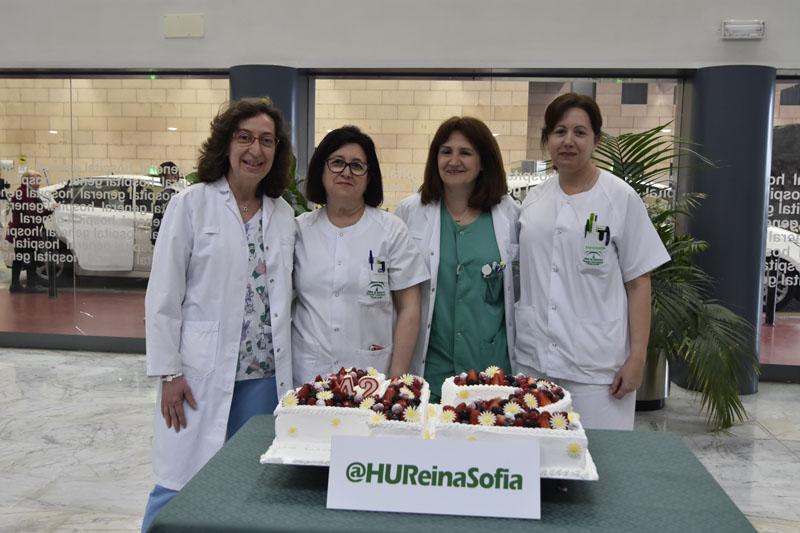 Profesionales de Enfermería Pediátrica posan junto a la tarta