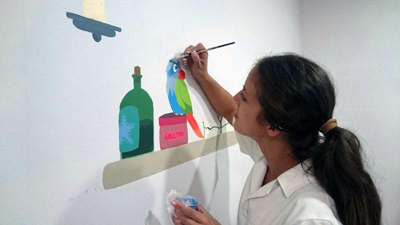 Una colaboradora pinta el loro.