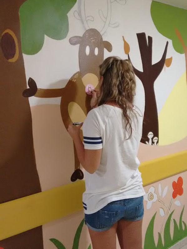 La diseñadora de la primera planta, Almudena Castillejo, dando color al gran ciervo que reina en el bosque