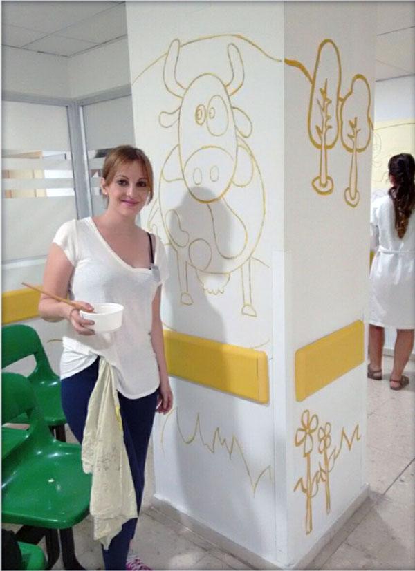 Otra de nuestras diseñadoras, María, con el mural de las vacas