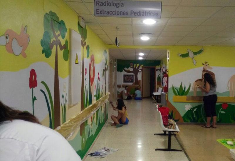 Voluntarios terminando de pintar la zona de la selva y la isla.